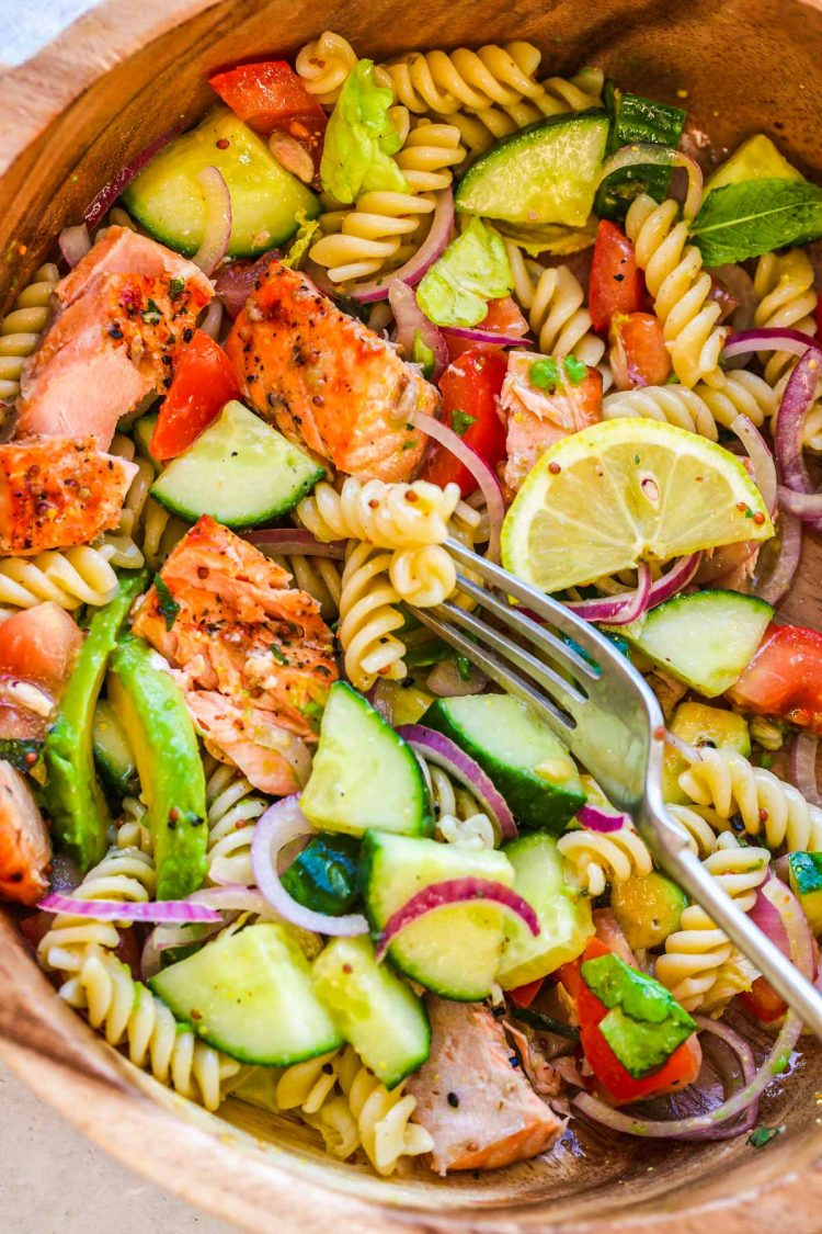 Overhead photo of a wooden serving bowl with salmon pasta salad in it.