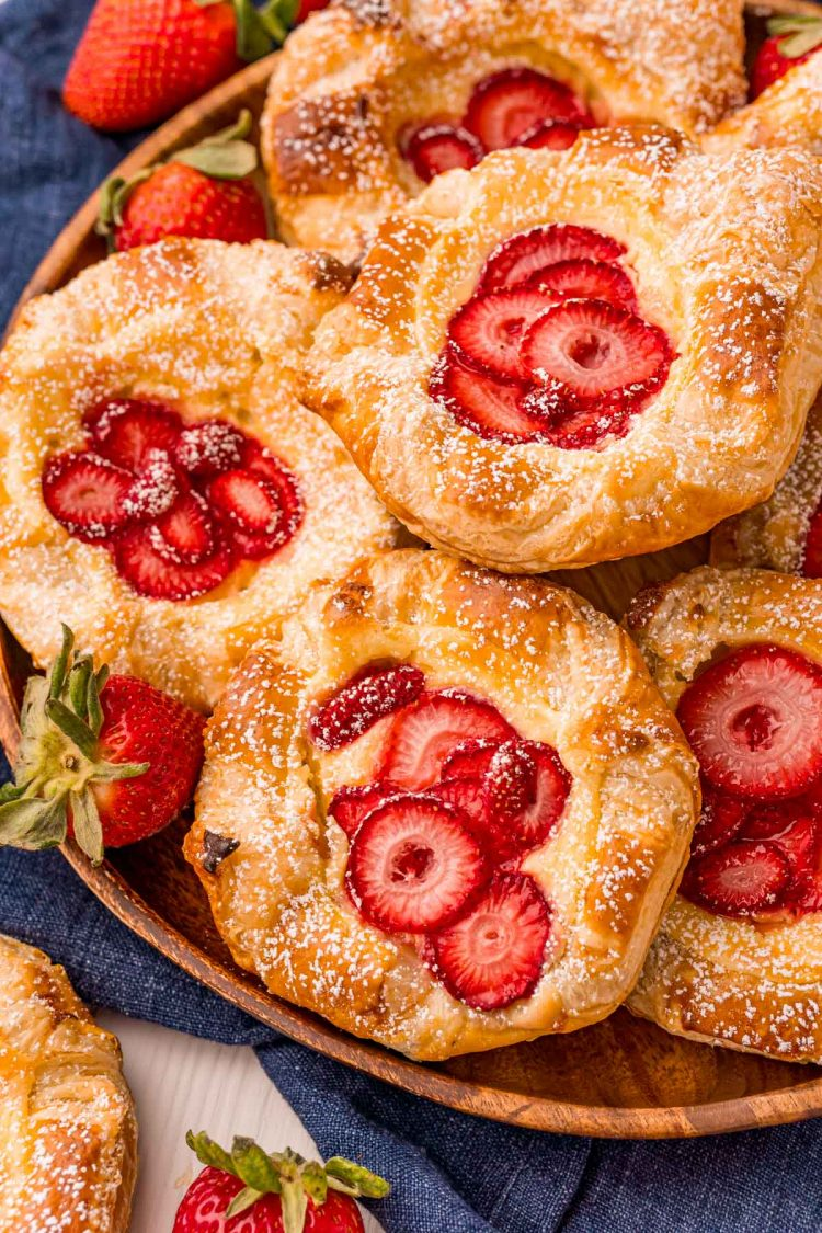 Close up photo of strawberry danishes on a wooden plate on a blue napkin.