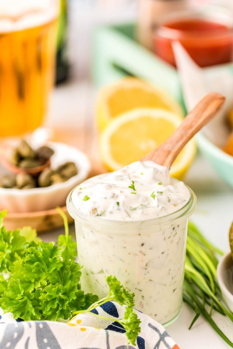 Tartar Sauce in a jar with a wooden spoon sticking out of it with ingredients in the background.