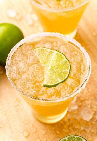 Close up photo og a glass with a beer margarita in it rimmed with sugar and garnished with lime wedges.