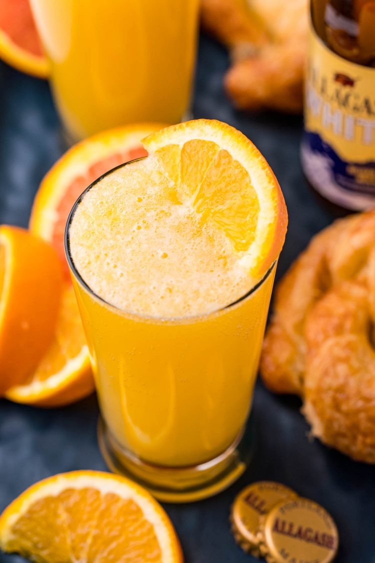 Close up photo of a beermosa surrounded by orange slices and croissants.