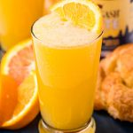Close up photo of a beermosa on a blue serving platter with croissants and oranges.