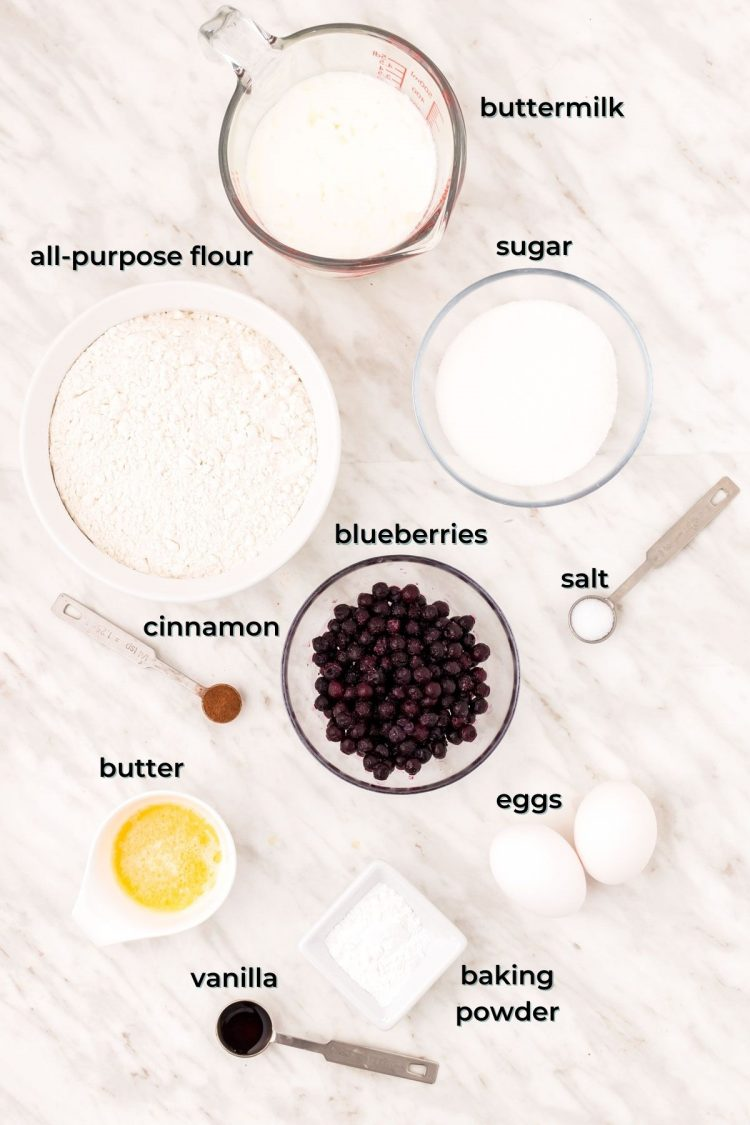 Ingredients to make blueberry donuts on a marble table.