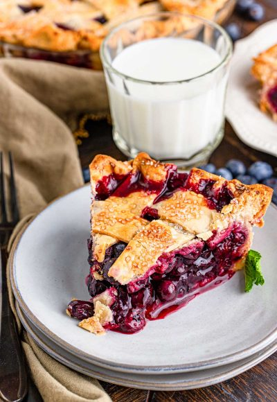 Close up photo of a slice of blueberry pie with a lattice crust on a white plate with more pie and a glass of milk in the background.