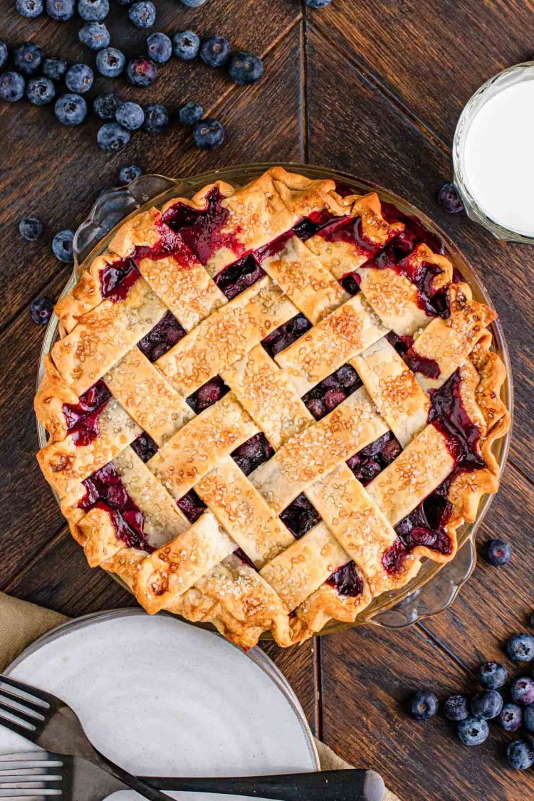 Overhead photo of a blueberry pie with a lattice crust on a wooden table.