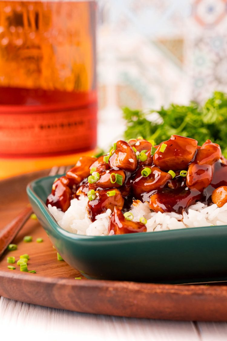 Close up photo of bourbon chicken and rice on a green plate on a wooden platter.