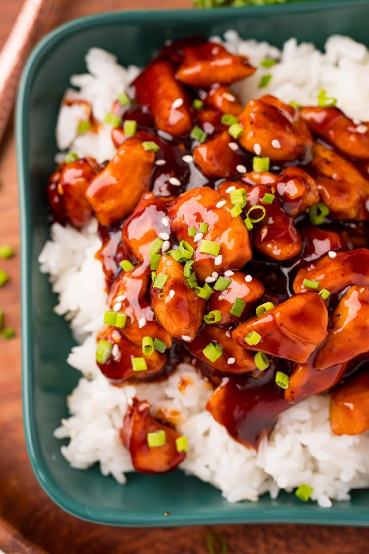 Close up photo of bourbon chicken on a bed of rice on a teal green dish.