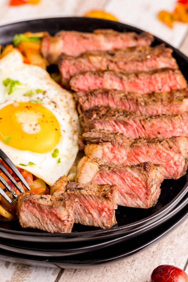 Close up photo of steak and eggs on a black plate.