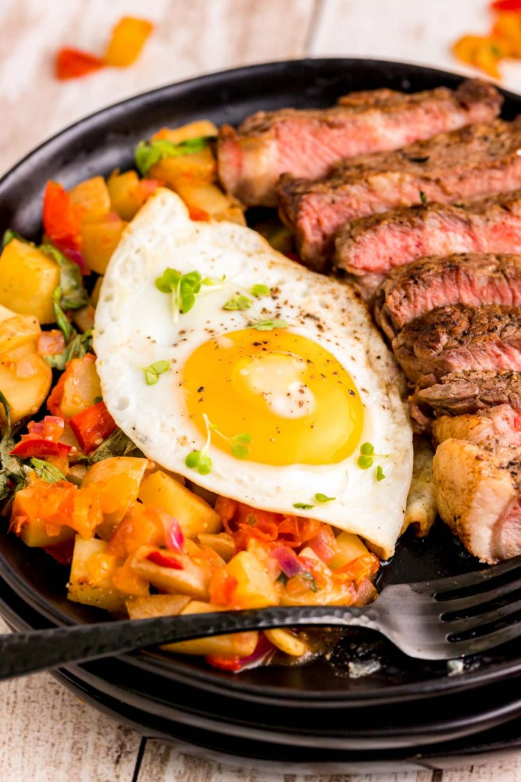 Close up photo of steak and eggs on a black plate with home fries.