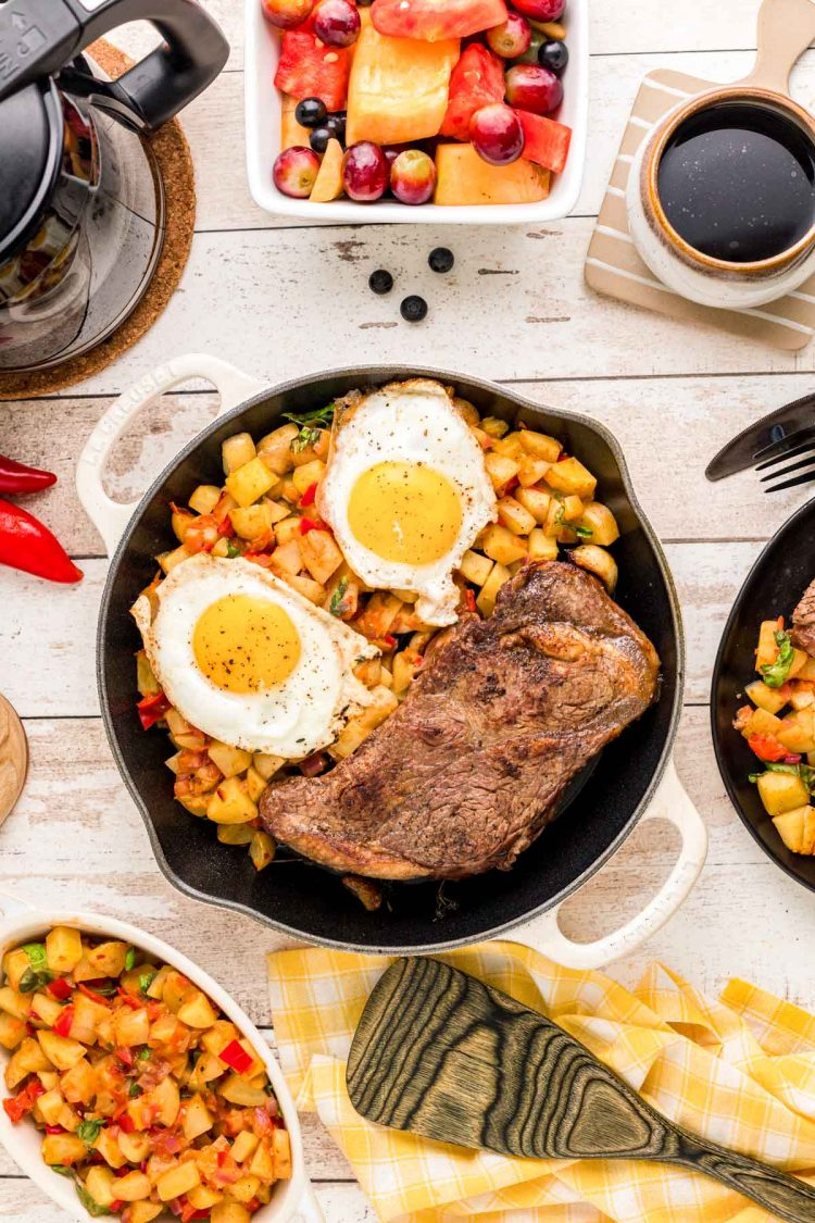 Overhead photo of steak and eggs on a skillet with home fries with coffee and plates around it.