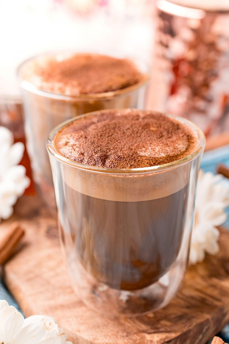 Close up photo of a double walled coffee glass filling with cafe con miel.