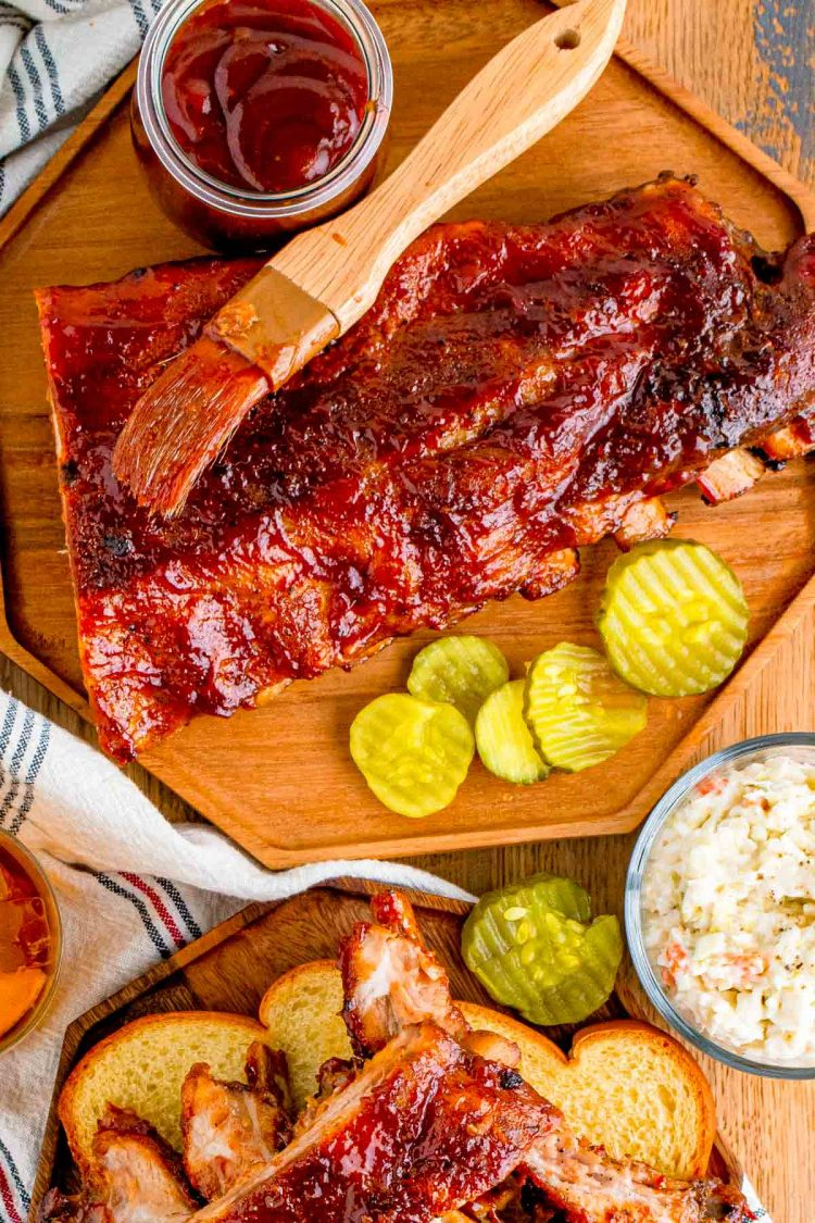 Overhead photo of ribs on a wooden plate with barbecue sauce and pickles.