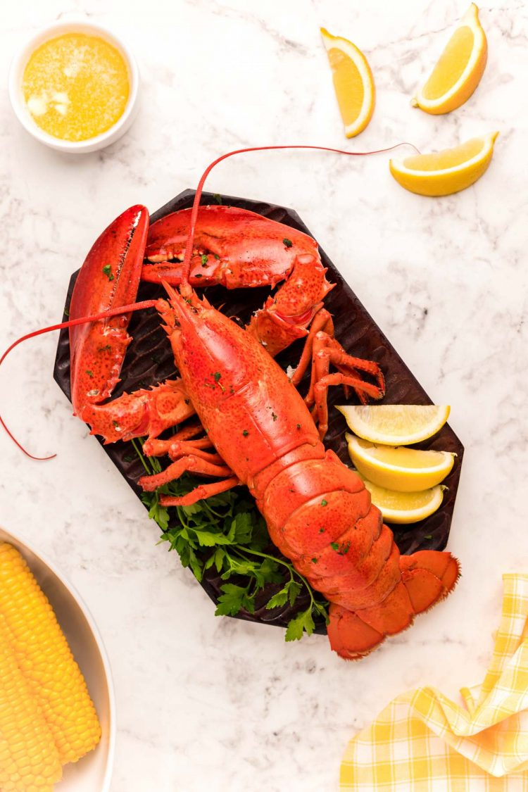 Overhead photo of a cooked lobster on a cutting board with lemon wedges and butter around it.