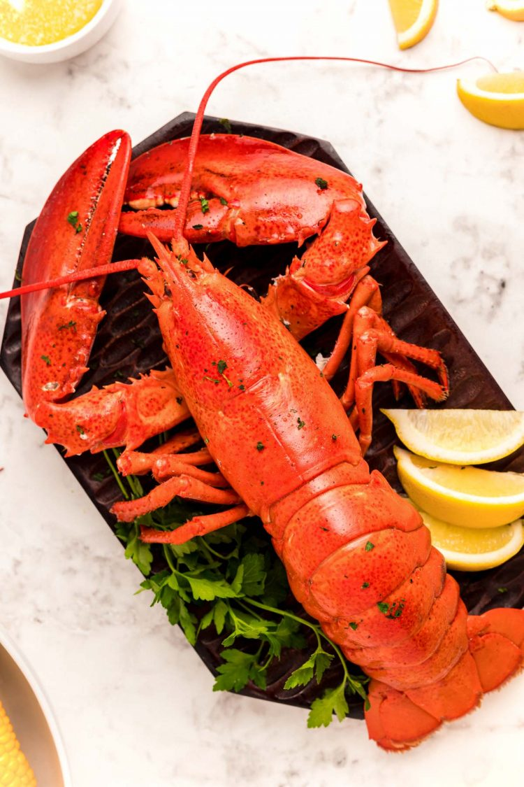 Close up photo of a steamed lobster on a cutting board with lemons.