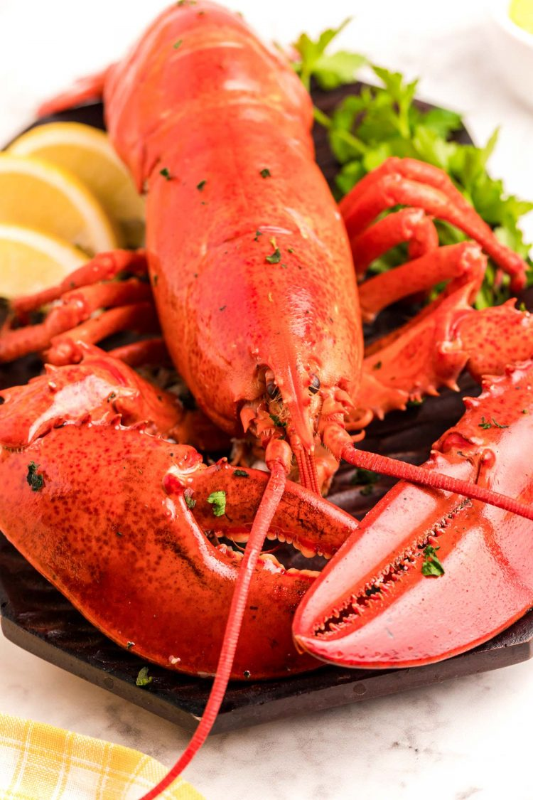 Close up photo of a cooked red lobster on a cutting board with herbs and lemon.