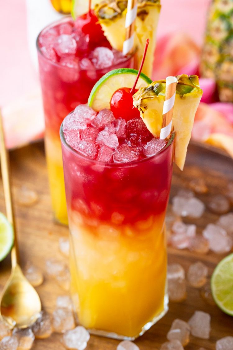 Close up photo of a Malibu Bay Breeze drink garnished with pineapple, cherry, and lime.