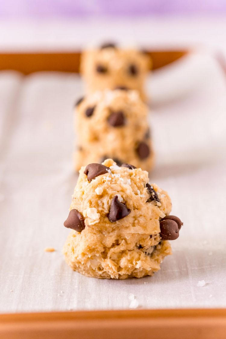 Close up photo of balls of cookie dough on a parchment lined baking sheet.