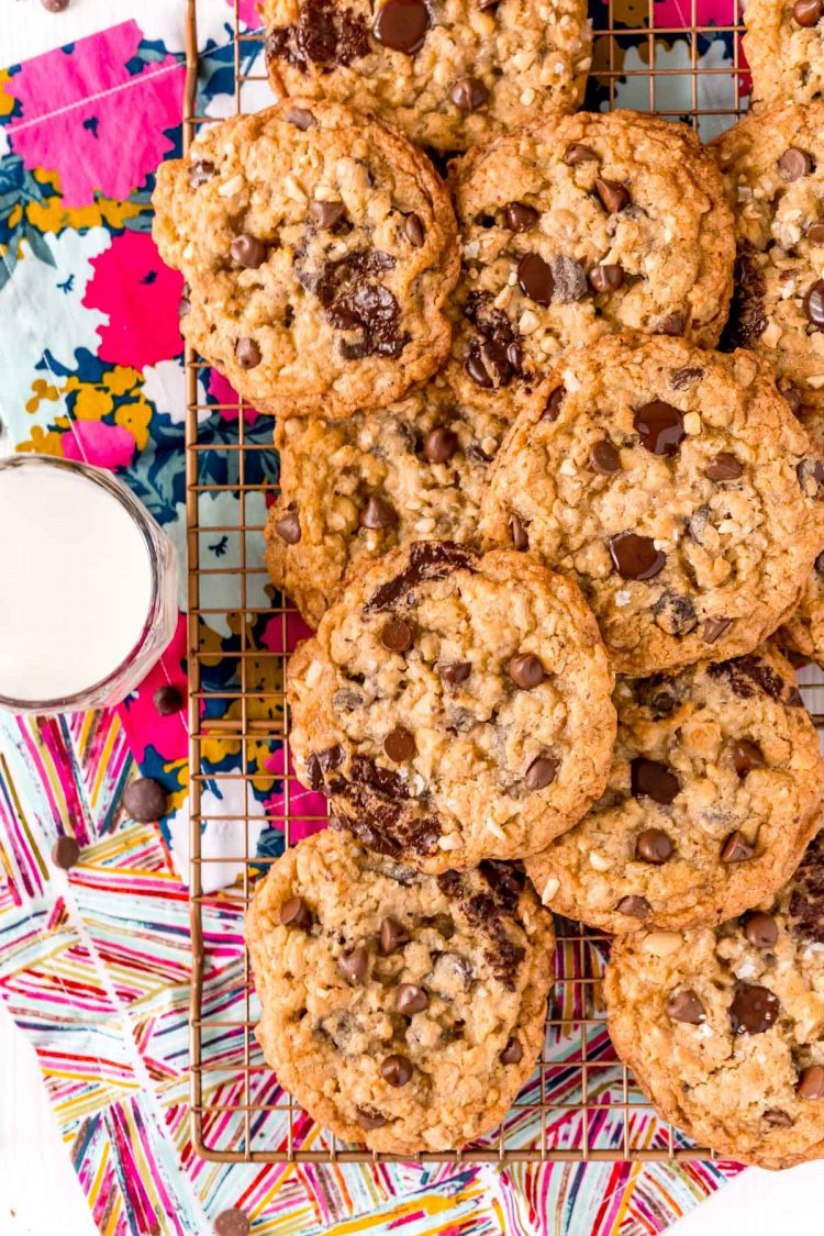 Overhead photo of ranger cookies on a wire rack on a colorful napkin with a glass of milk next to it.