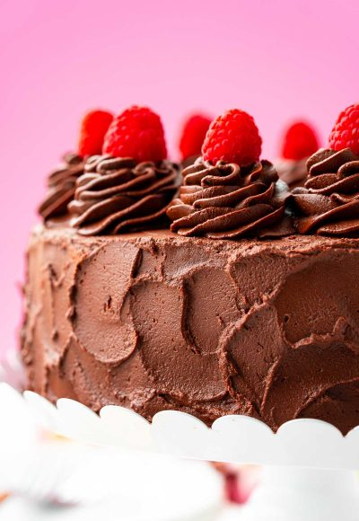 Close up photo of a dark chocolate cake topped with raspberries.