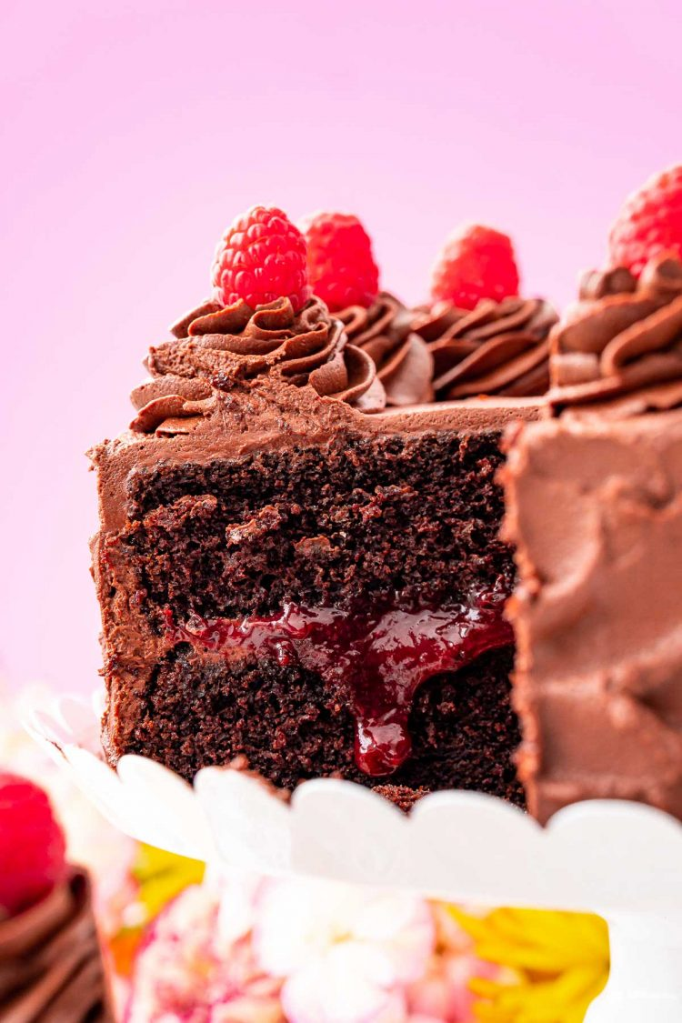 Close up photo of a chocolate cake with raspberry filling on a white cake stand.