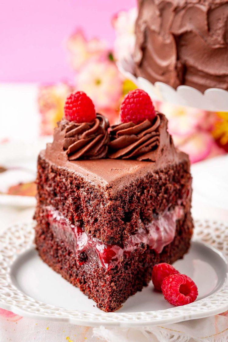 Close up photo of a slice of raspberry chocolate cake on a white plate.