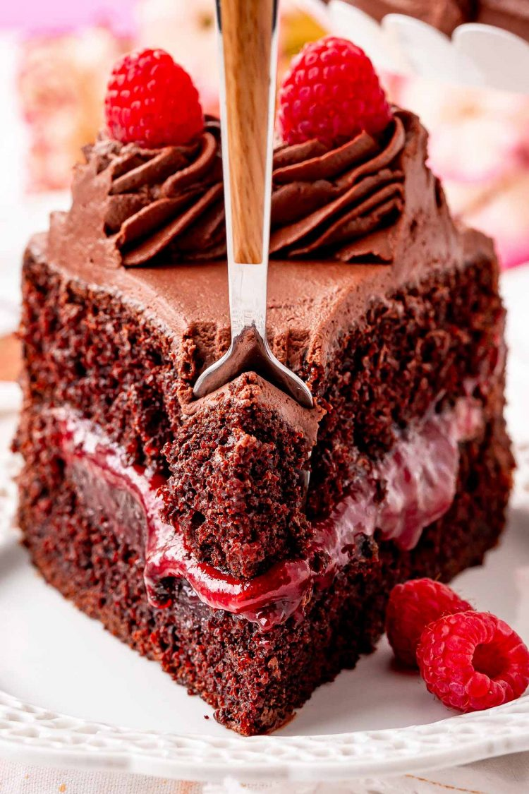 Close up photo of a fork taking a bite out of a slice of chocolate raspberry cake on a white plate.