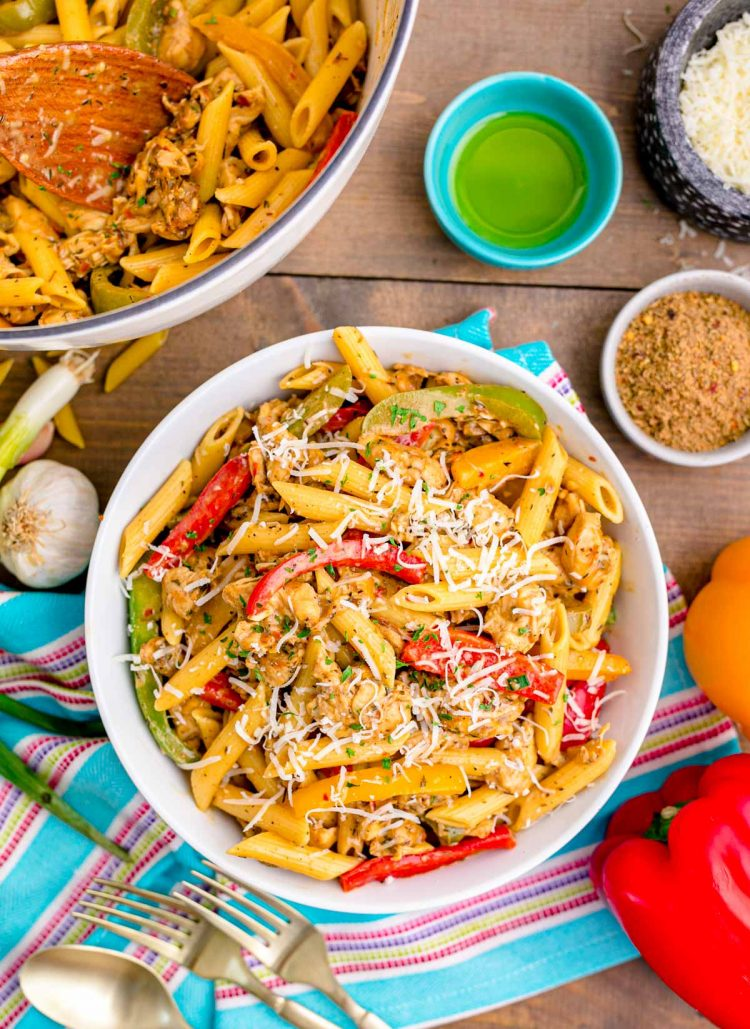 Overhead photo of a bowl of rasta pasta on a wooden table surrounded by ingredients.