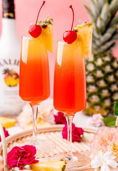 Close up photo of two Hawaiian Mimosas in champagne sluted garnished with pineapple wedges and cherries.