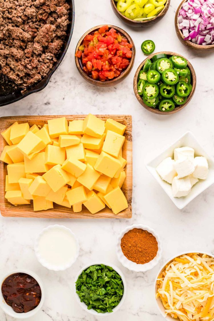 Overhead photo of ingredients to make smoked queso dip on a marble counter.