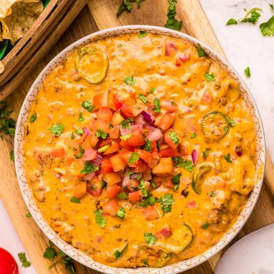 A bowl of smoked queso dip on a wooden cutting board.