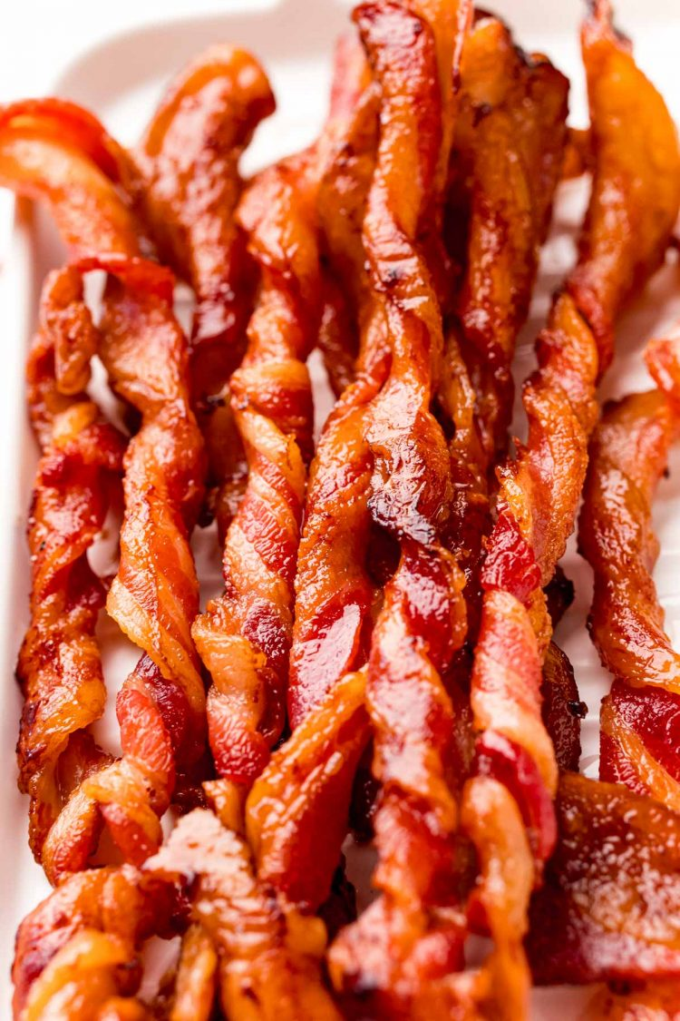 Close up photo of twisted bacon on a white serving tray.