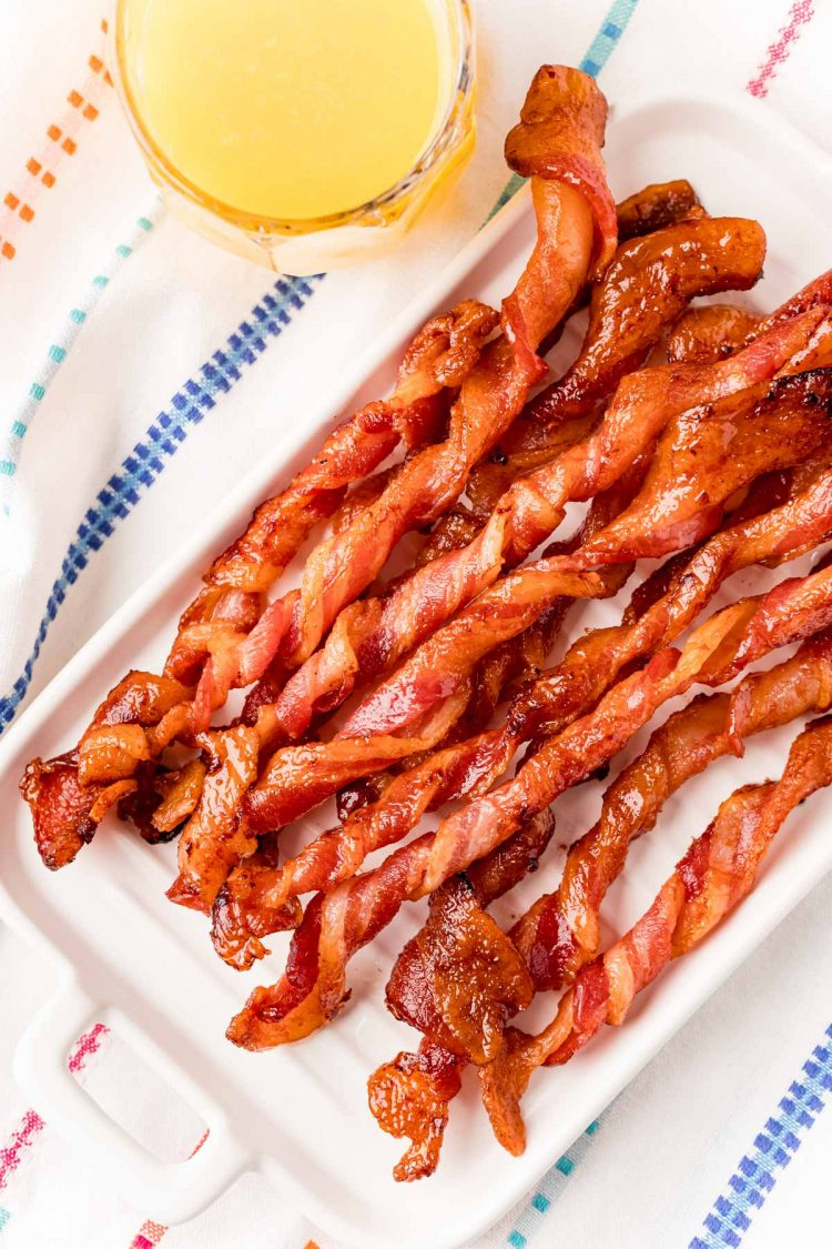 Close up photo of twisted bacon on a white plate with a glass of orange juice next to it.