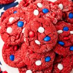 Overhead photo of red velvet cake mix cookies with red, white, and blue M&M's on a white plate on a blue star napkin.