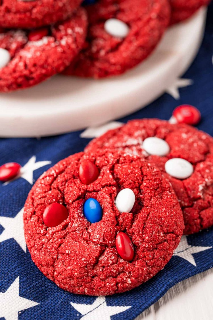 Close up photo of two red velvet cookies on a blue and white striped napkin with more cookies in the background.