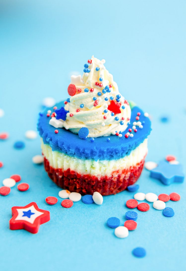 A red, white, and blue mini cheesecake sitting on a blue surface with sprinkles all around.