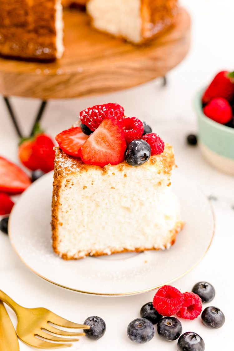 Close up photo of a slice of angel food cake topped with berries on a white plate.