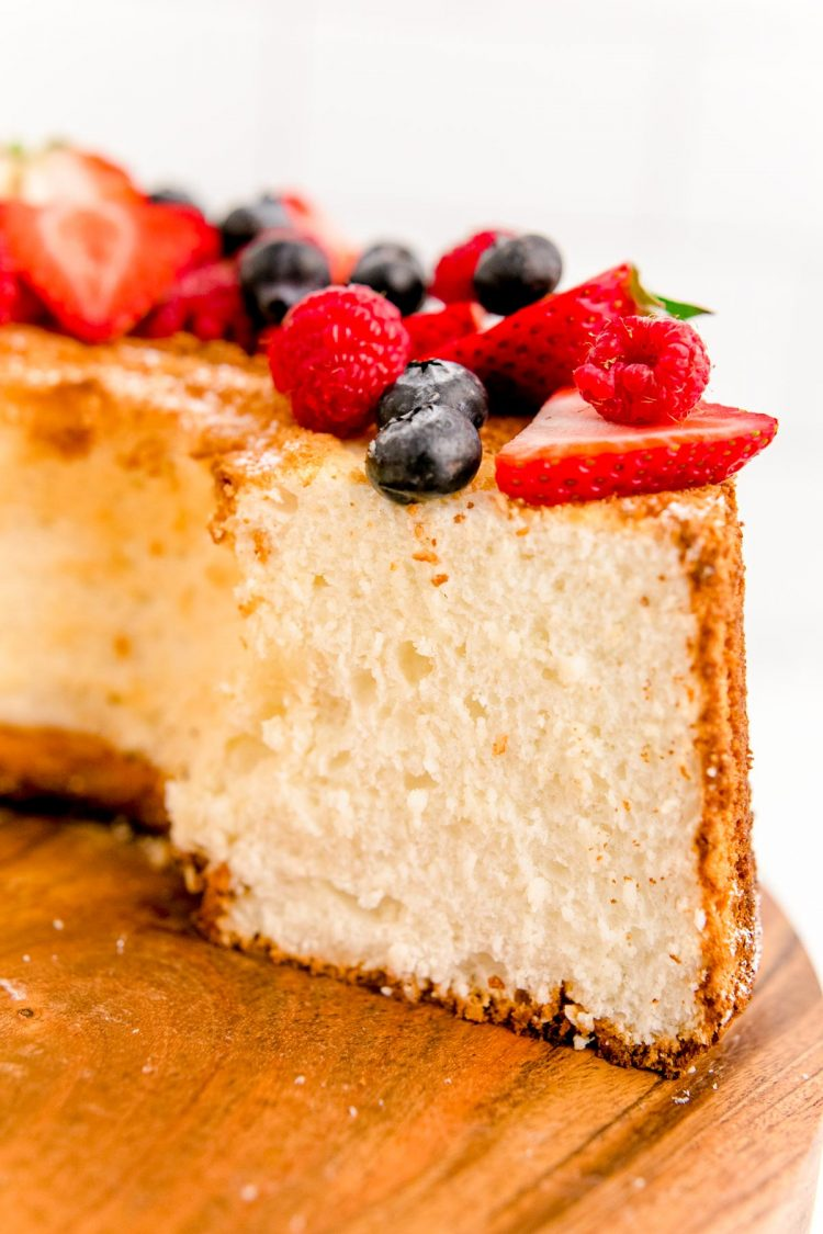 Close up photo of angel food cake on a wooden cake stand with a slice missing.