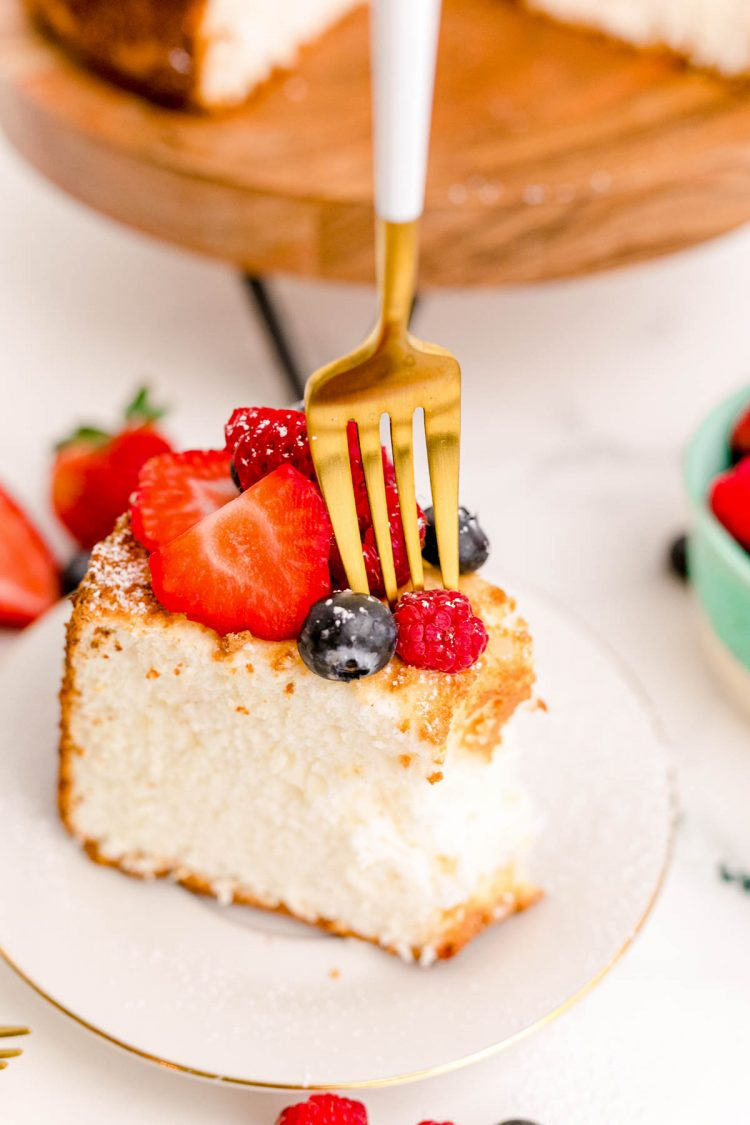 A fork taking a bite of angel food cake on a white plate topped with berries.