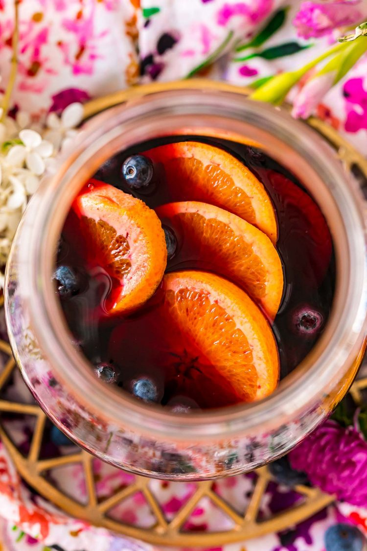 Overhead photo of a pitcher filled with blueberry sangria with orange slices and blueberries.