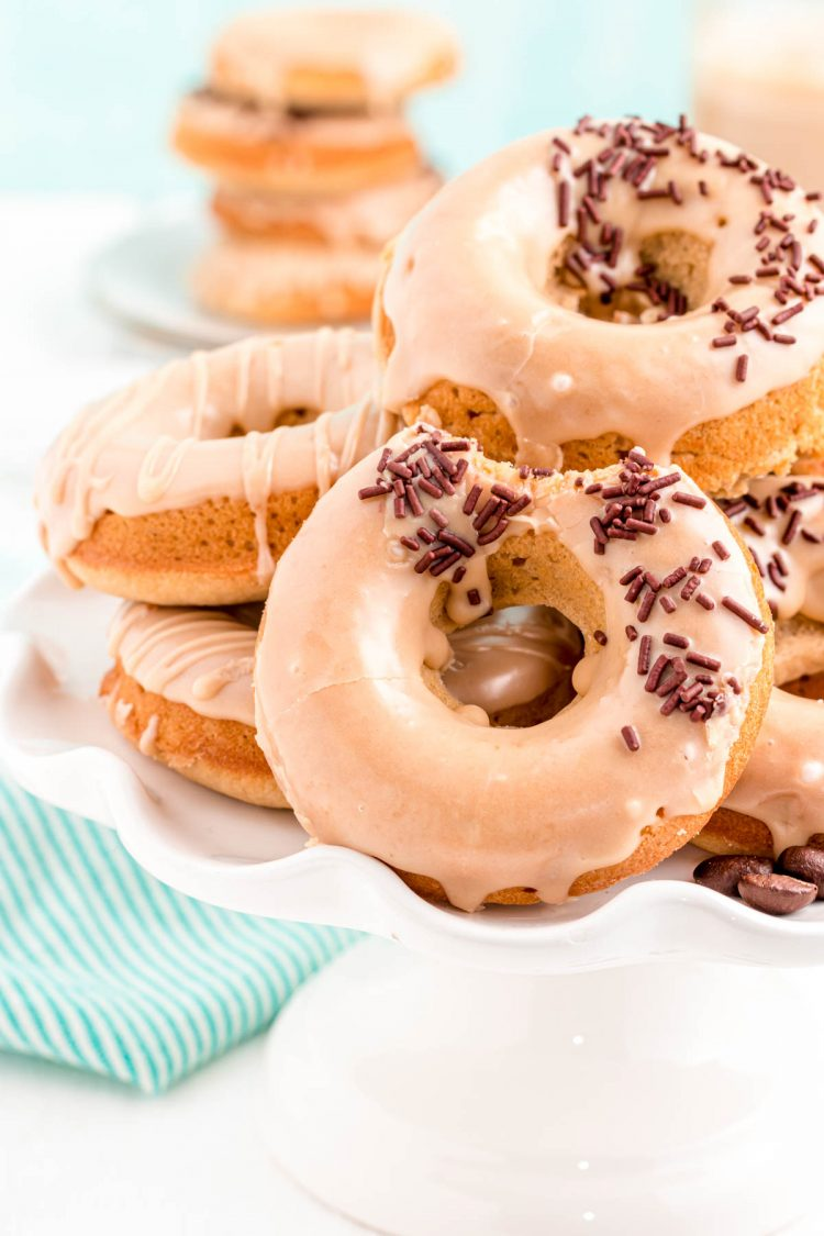 Close up photo of coffee donuts on a white cake stand with a teal napkin in the background.