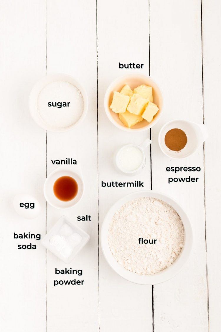 Overhead photo of ingredients prepped to make coffee donuts on a white wooden table.
