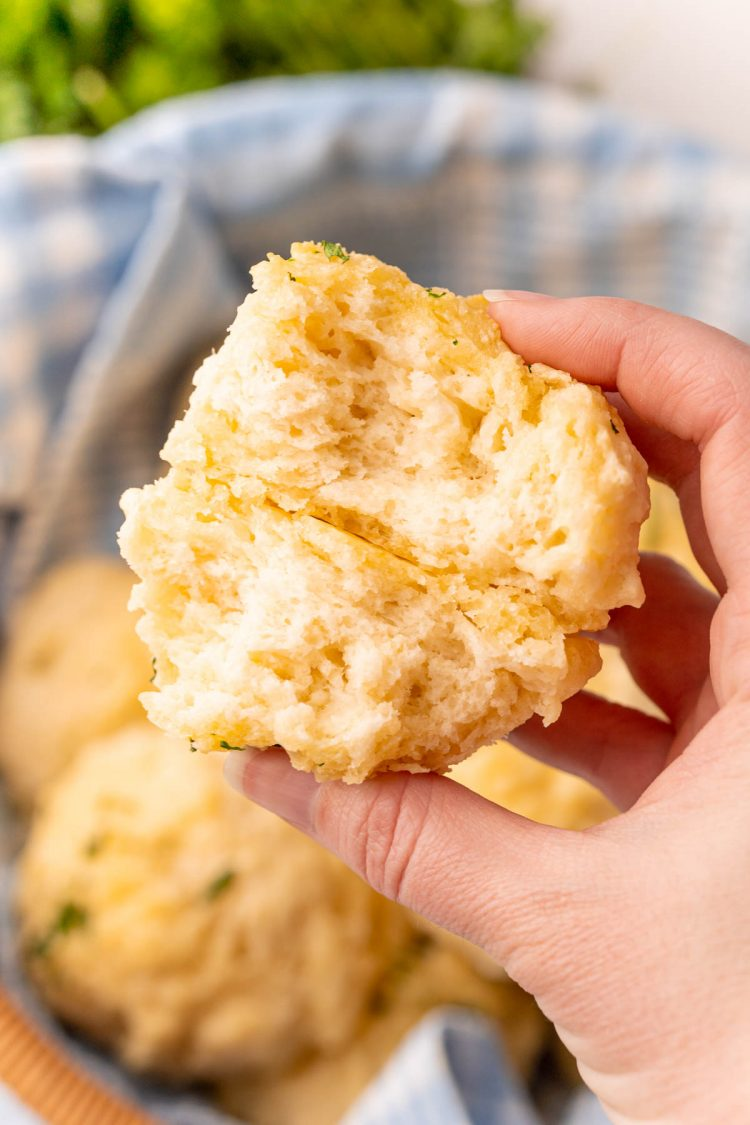 A woman's hand holding a drop biscuit that has been broken in half to show the texture.