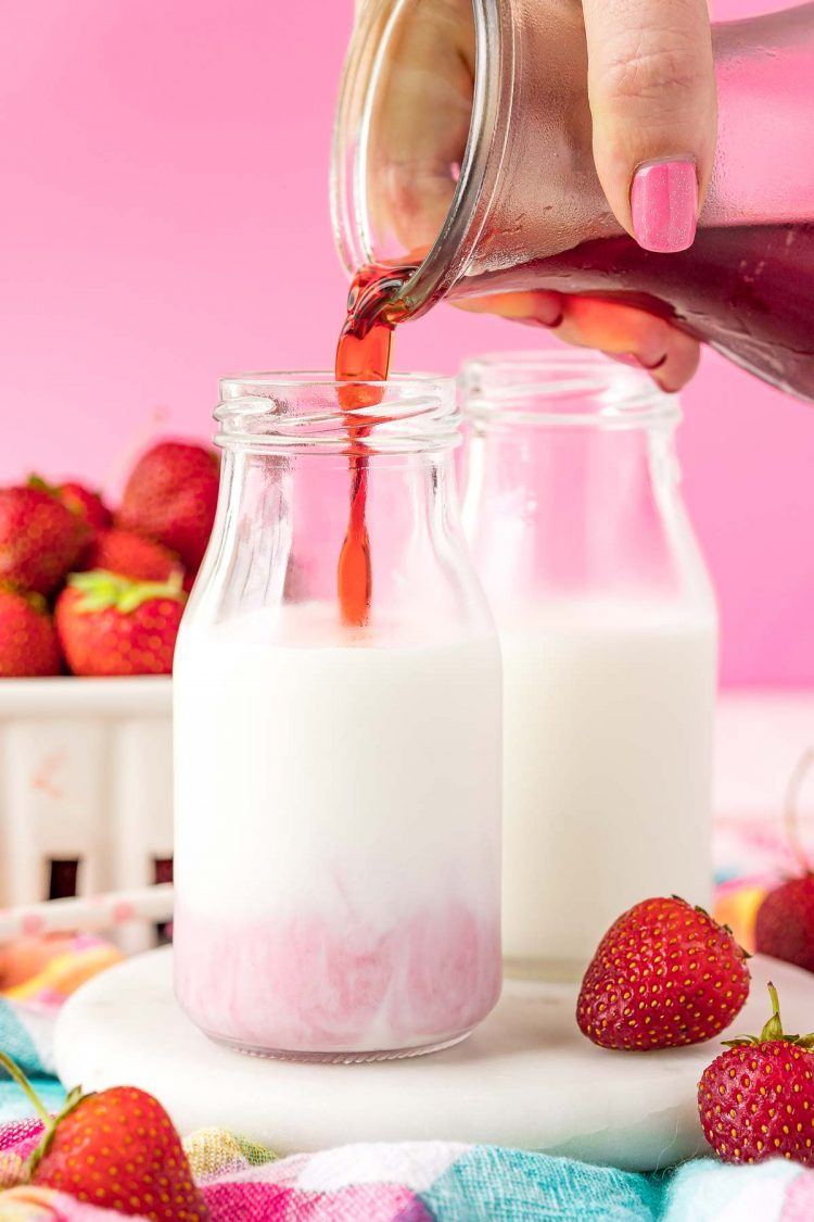 Strawberry simple syrup being poured into a bottle of milk.