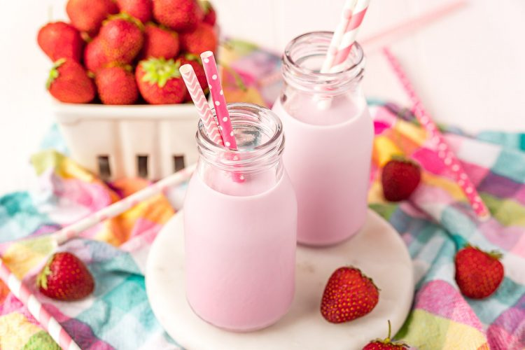 Close up horizontal photo of two milk bottles with strawberry milk and pink straws in them on a white board on a colorful napkin.