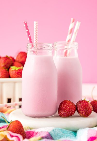 Close up photo of two milk bottles of homemade strawberry milk on a white board.