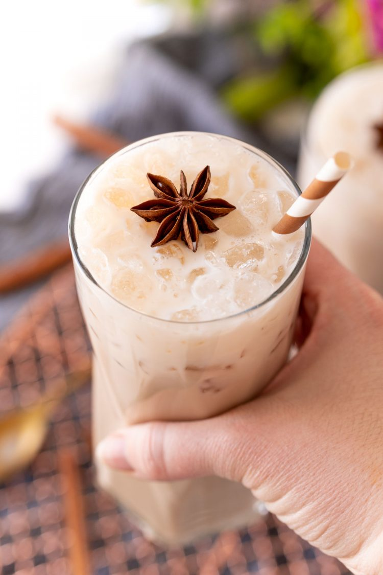 A woman's hand holding a glass with an iced chai latte to the camera.