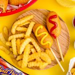 Close up photo of mini corn dogs on a wooden plate with crinkle fries.