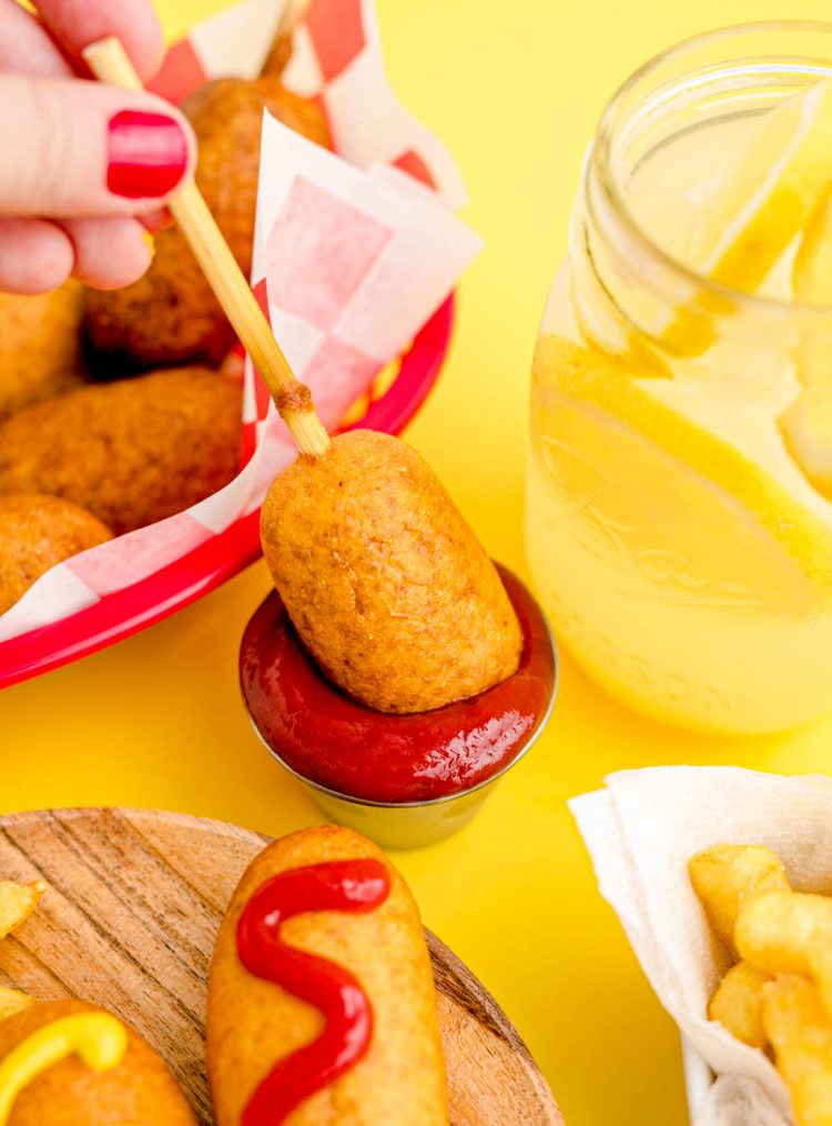 A mini corndog being dipped in a small bowl of ketchup.
