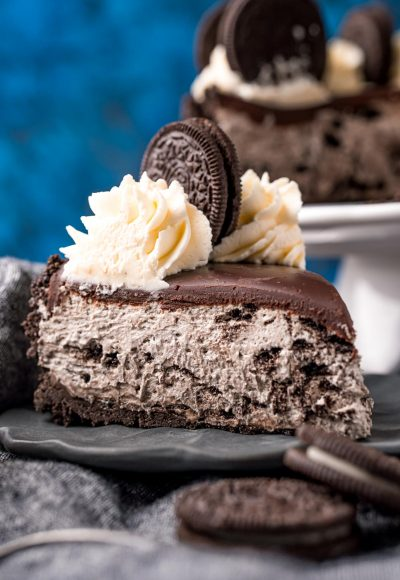 Close up photo of a slice of no bake oreo cheesecake on a gray plate on a gray napkin with oreos around it.
