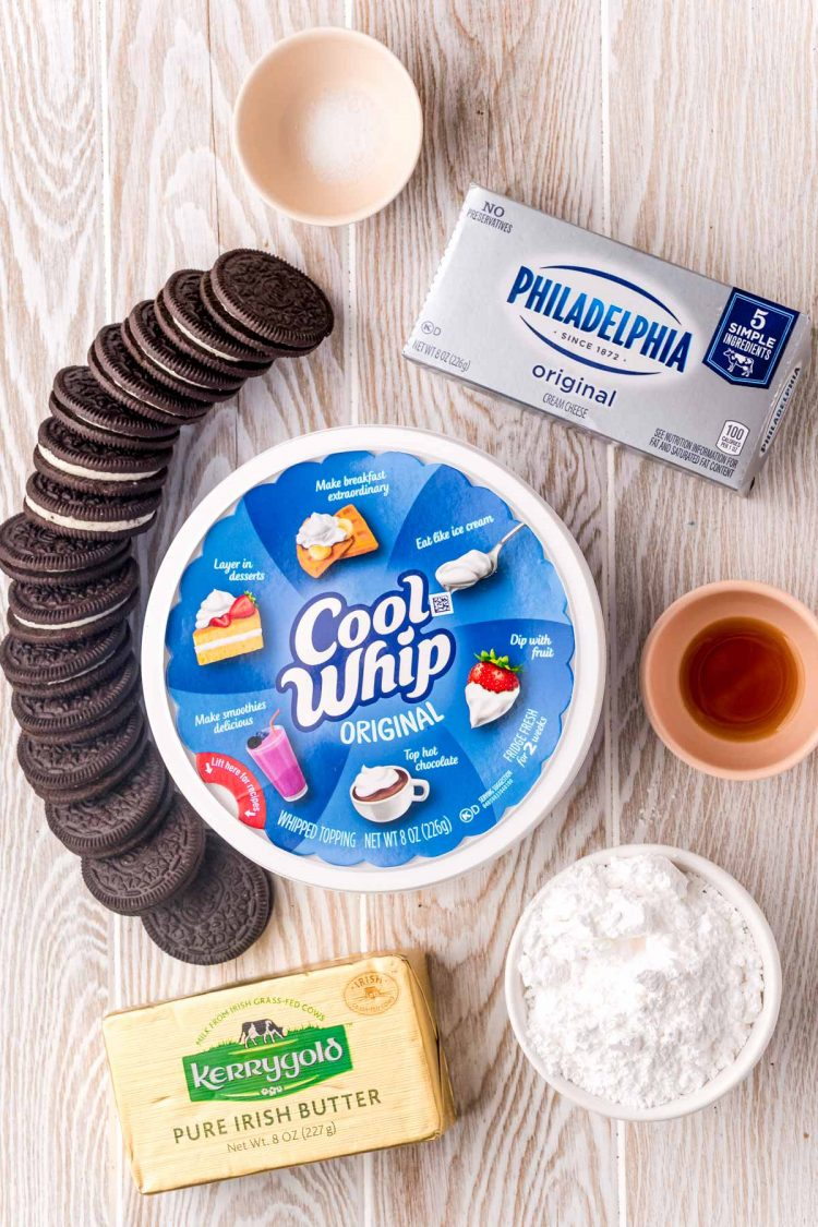 Overhead photo of ingredients to make Oreo no bake cheesecake on a white washed wood surface.